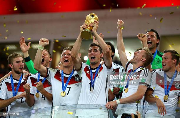 Miroslav Klose of Germany lifts the World Cup trophy to celebrate with his teammates during the award ceremony after the 2014 FIFA World Cup Brazil...