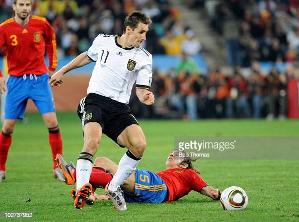 Miroslav Klose of Germany tackled by Carles Puyol of Spain during the 2010 FIFA World Cup South Africa Semi Final match between Germany and Spain at...