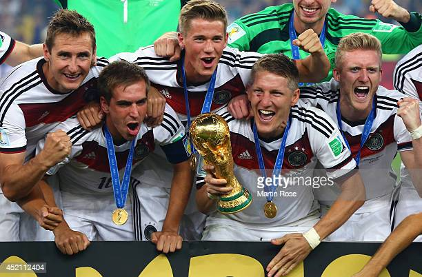 Miroslav Klose Philipp Lahm Erik Durm Bastian Schweinsteiger and Toni Kroos of Germany celebrate with the World Cup trophy after defeating Argentina...