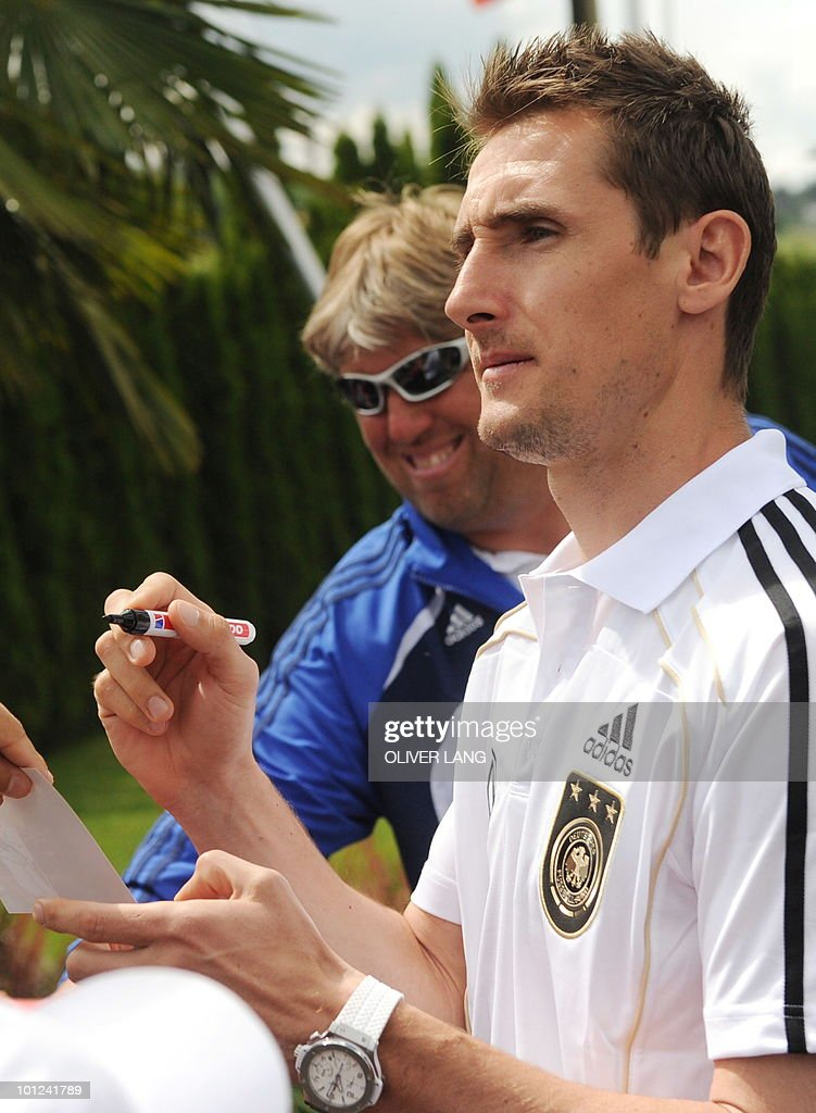 Miroslav Klose (R), striker of the German national football team, gives autographs to young supporters at the team's training camp in Appiano near the north Italian city of Bolzano May 28, 2010. The German football team is currently taking part in a 12-day training camp in Appiano to prepare for the upcoming FIFA Football World Cup in South Africa.