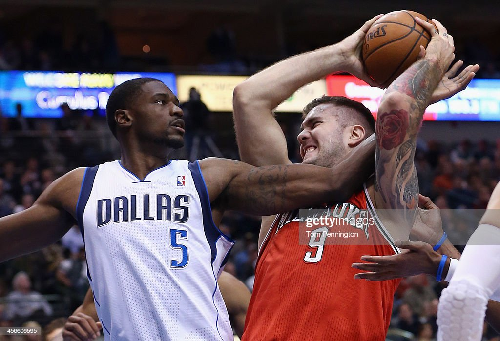 Miroslav Raduljica #9 of the Milwaukee Bucks drives to the basket against Bernard James #5 of the Dallas Mavericks in the third quarter at American Airlines Center on December 14, 2013 in Dallas, Texas.