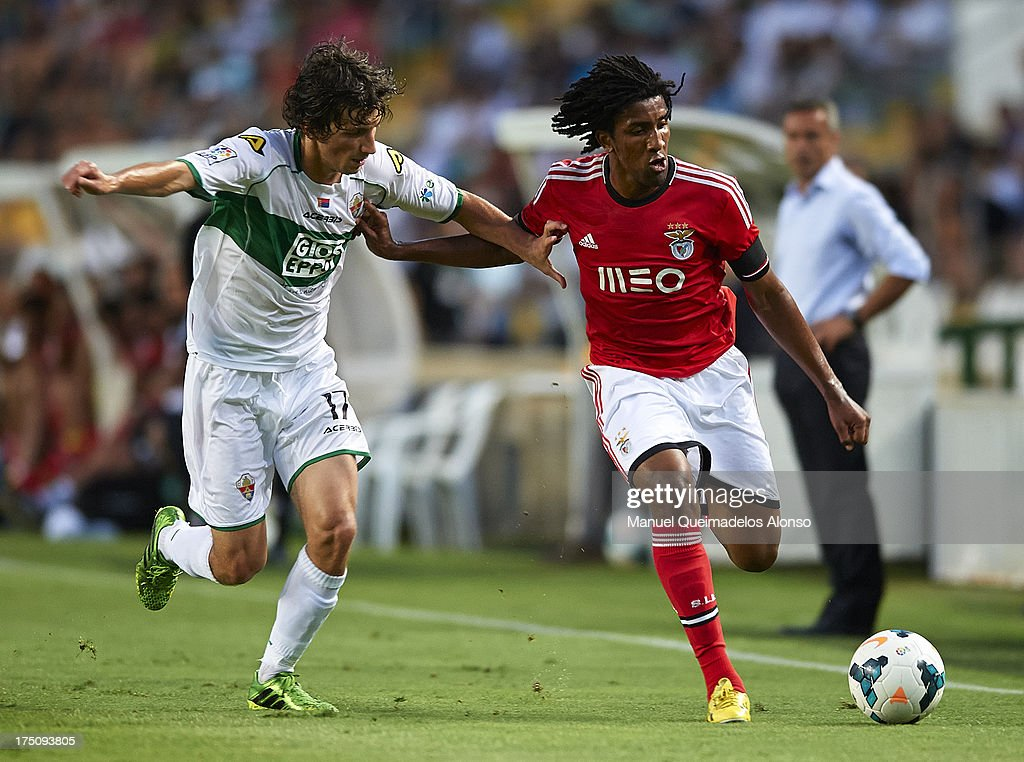 Miroslav Stevanovic (L) of Elche competes for the ball with Bruno Cortez of Benfica during a friendly match between Elche CF and Benfica at Estadio Martinez Valero on July 31, 2013 in Elche, Spain.