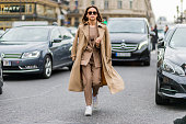 Miroslava Duma wearing a beige suit and trench coat and white sneaker outside Stella McCartney during the Paris Fashion Week Womenswear Fall/Winter...