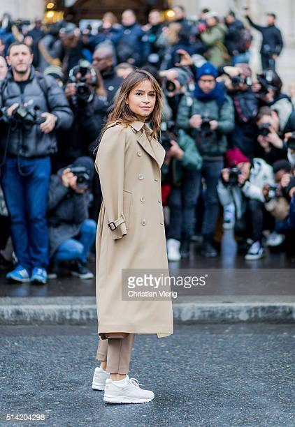 Miroslava Duma wearing a beige suit and trench coat and white sneaker posing in front of photographers outside Stella McCartney during the Paris...