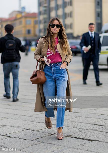 Miroslava Duma wearing a trench coat a Coca Cola shirt blue denim jeans Gucci shoes and a Loewe bag seen outside Gucci during Milan Fashion Week...