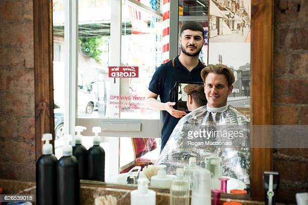 Mirror image of barber using mirror to show smiling customer haircut
