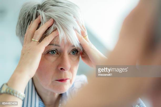 Mirror image of senior woman watching herself