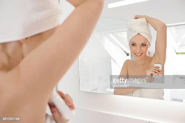 Mirror image of woman applying deodorant in the bathroom