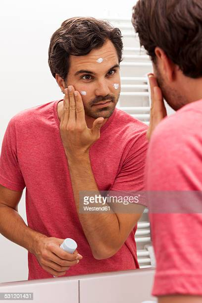 Mirror image of young man applying face cream