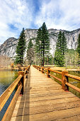 Mirror Lake Yosemite national park and wooden bridge. This is a view of Mirror Lake with the reflections of the trees and mountains in the background.