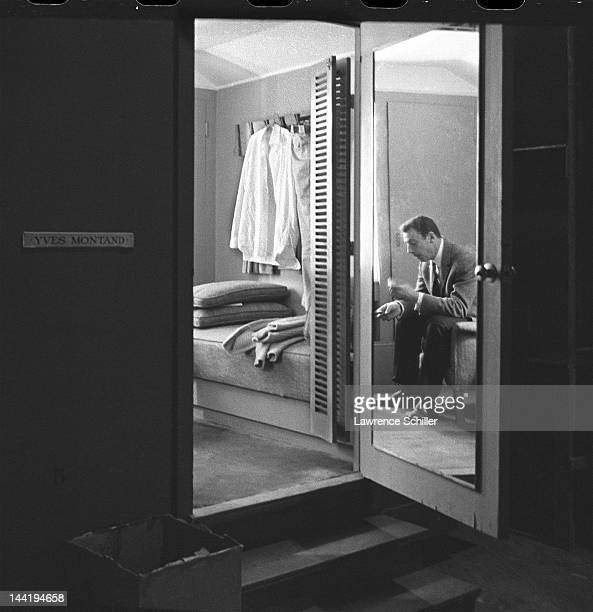 APPLY A mirror on the door reflects French actor Yves Montand as he sits in his dressing room on the set of 'Let's Make Love' Los Angeles California...