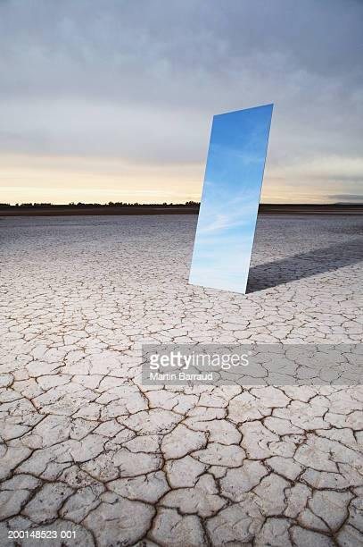 Mirror reflecting sky in bare landscape