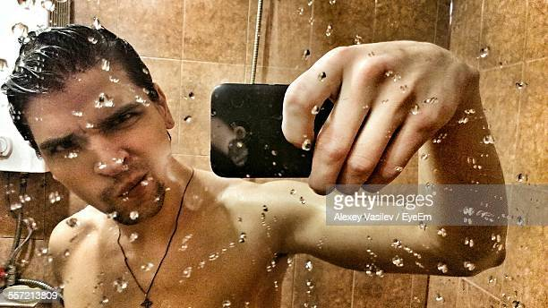 Mirror Reflection Of Man Taking Self Portrait In Bathroom