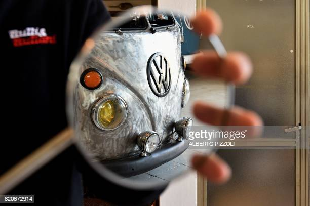 A mirror reflects a vintage Volkswagen Kombi bus restored by the 'T1 specialist' team on November 3 2016 at the garage Nucci in Florence Campers like...
