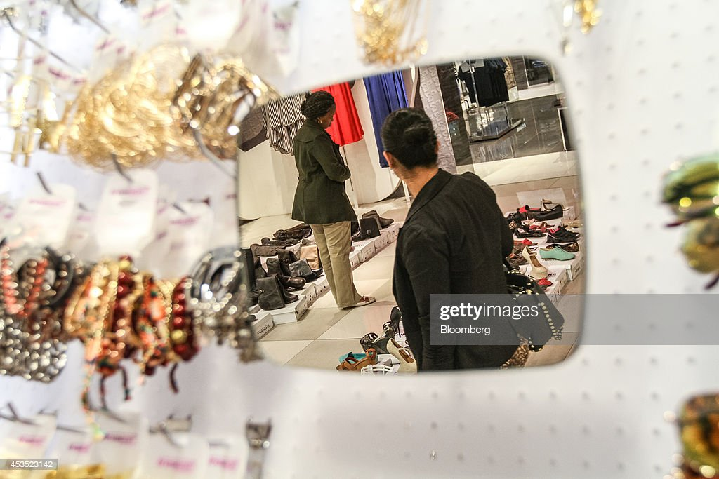 A mirror reflects customers browsing women's footwear for sale inside a Truworths International Ltd fashion store in Sandton South Africa on Tuesday...