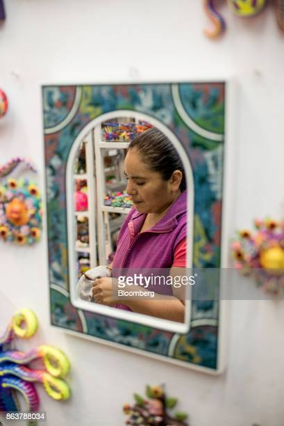 A mirror reflects the image of a worker cleaning an alebrije Mexican folk art sculpture to display for sale at the Ciudadela Market in Mexico City...