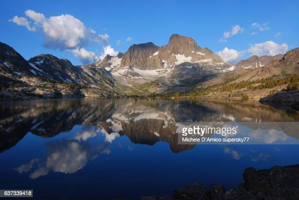Mirror-like reflections of mighty peaks in an alpine lake