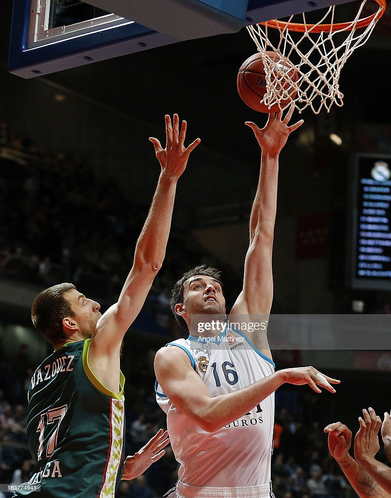 Mirza Begic #16 of Real Madrid aims to shoot against Fran Vazquez #17 of Unicaja Malaga during the Turkish Airlines Euroleague Top 16 game at Palacio de los Deportes on March 15, 2013 in Madrid, Spain.