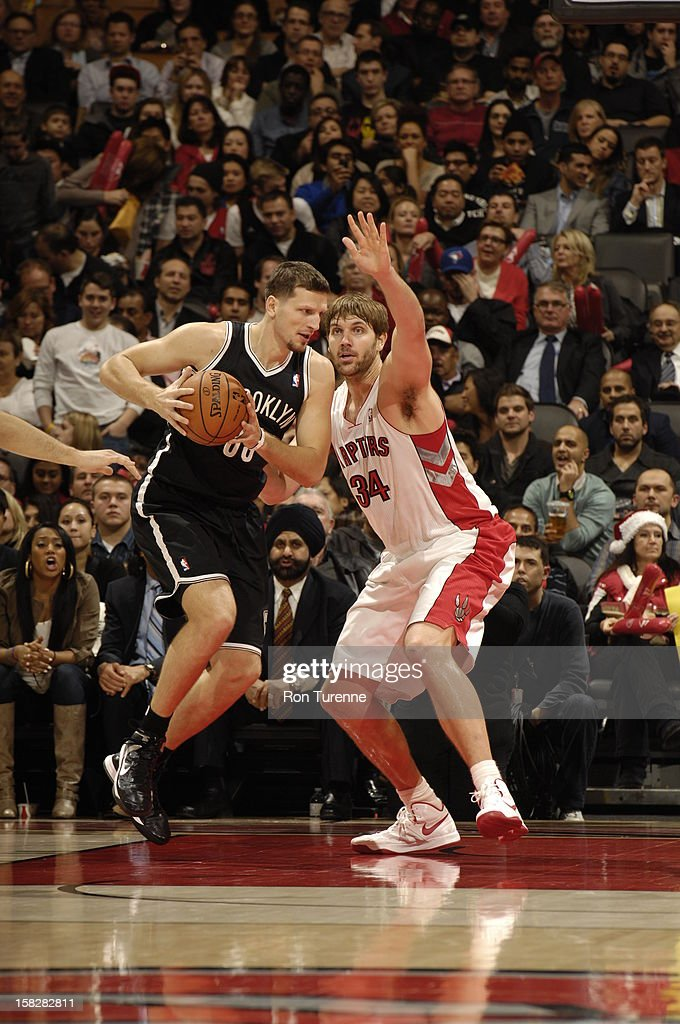 Mirza Teletovic #33 of the Brooklyn Nets controls the ball against Aaron Gray #34 of the Toronto Raptors on December 12, 2012 at the Air Canada Centre in Toronto, Ontario, Canada.