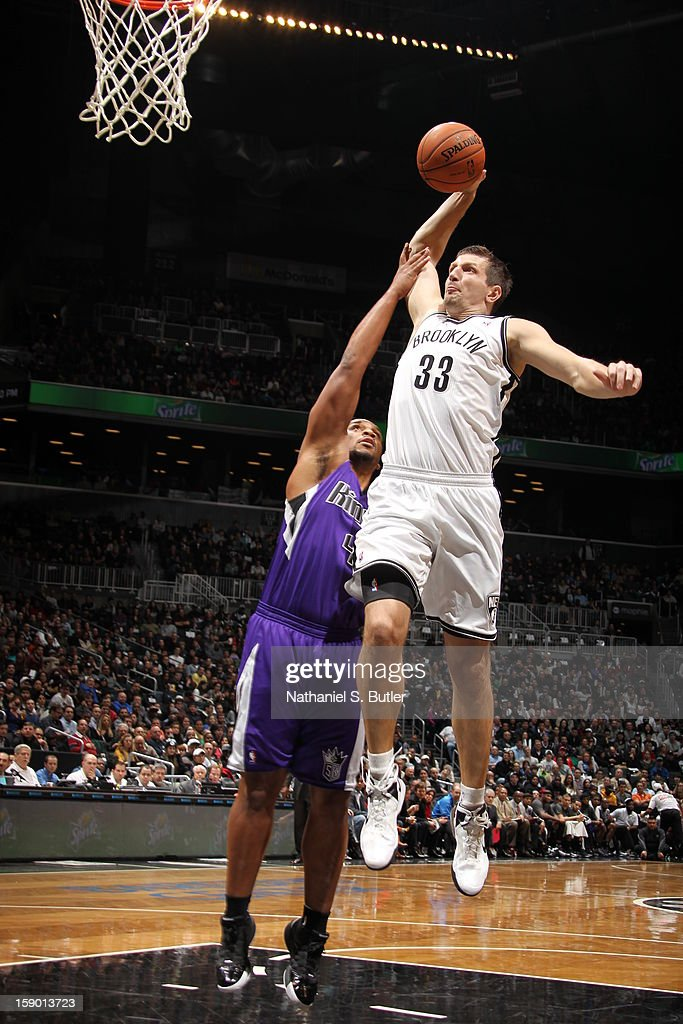 Mirza Teletovic #33 of the Brooklyn Nets dunks against Chuck Hayes #42 of the Sacramento Kings on January 5, 2013 at the Barclays Center in the Brooklyn borough of New York City.