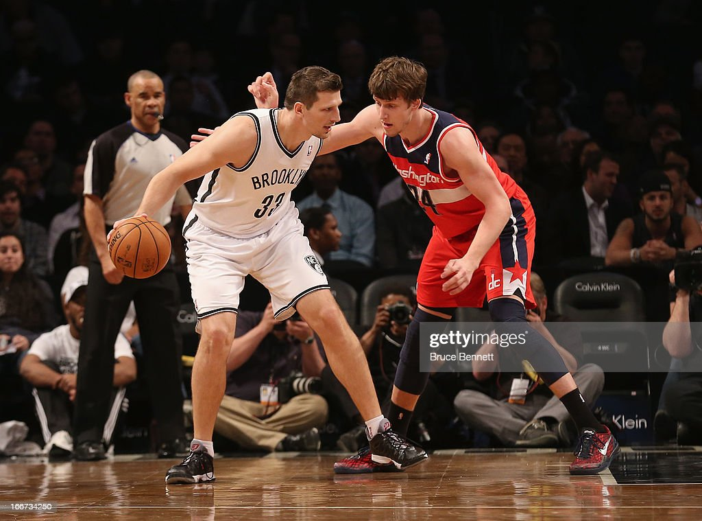 Mirza Teletovic of the Brooklyn Nets slaps away the hand of Jan Vesely of the Washington Wizards and is penalized at the Barclays Center on April 15...