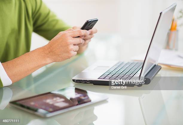 Mis section of man using mobile phone at desk