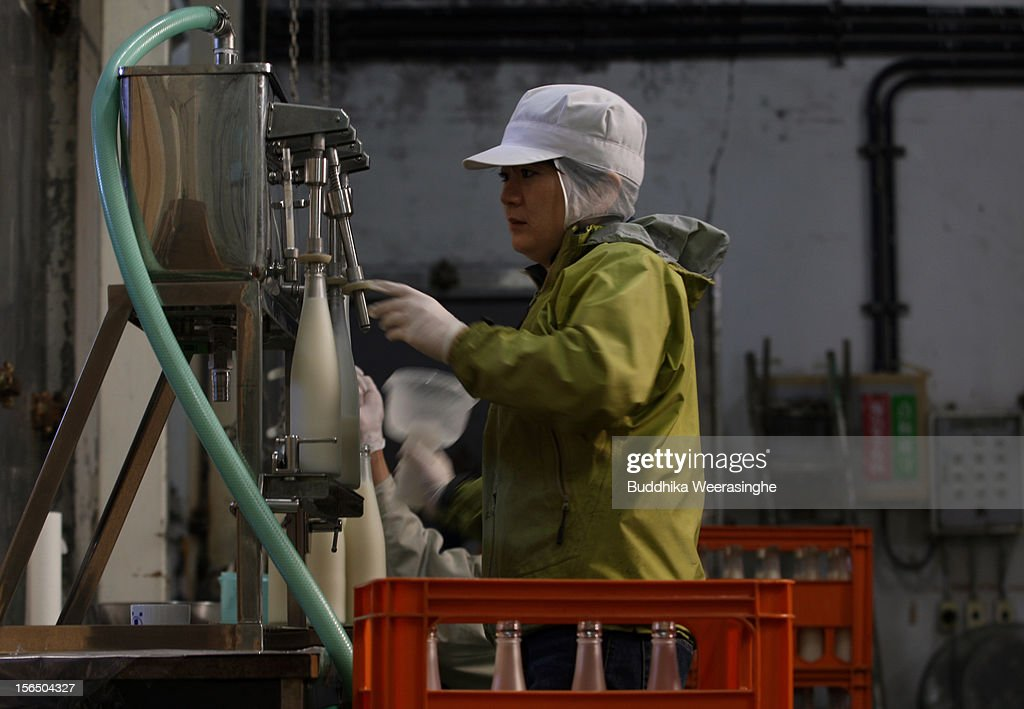 Misa Kawaisi, chief sake brew master, fills sake bottles at Nadagiku-Shozo sake brewery on November 16, 2012 in Himeji, Japan. Kawaishi, one of a few female sake brew masters, is a unique figure in male-diminated sake brewers world.