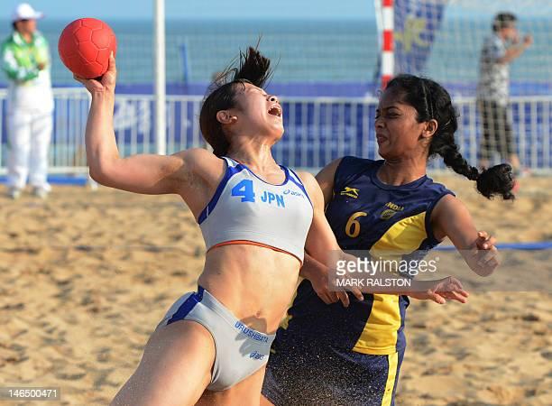 Misa Urushibata of Japan is blocked by Thanu Mathew of India before winning their women's beach handball match 20 at the 3rd Asian Beach Games in...