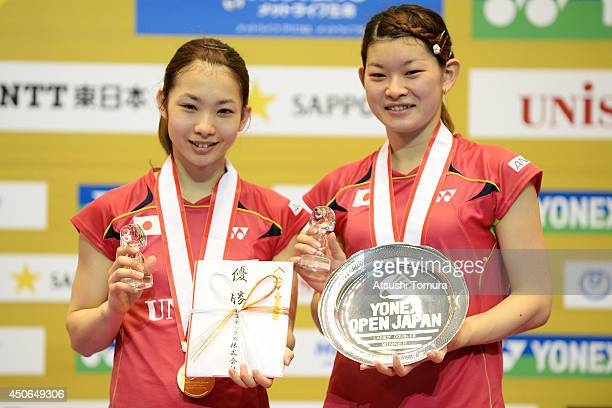 Misaki Matsutomo and Ayaka Takahashi of Japan celebrate with the gold medal on the podium during day six of Badminton YONEX Open on June 15 2014 in...
