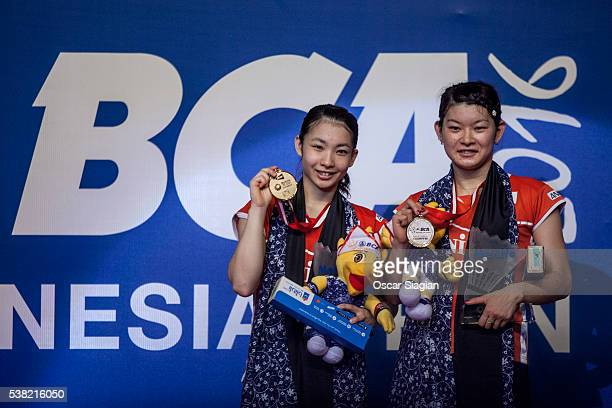 Misaki Matsutomo and Ayaka Takahashi of Japan pose on the podium after winning the 2016 Indonesia Open final match against Tang Yuanting and Yu Yang...