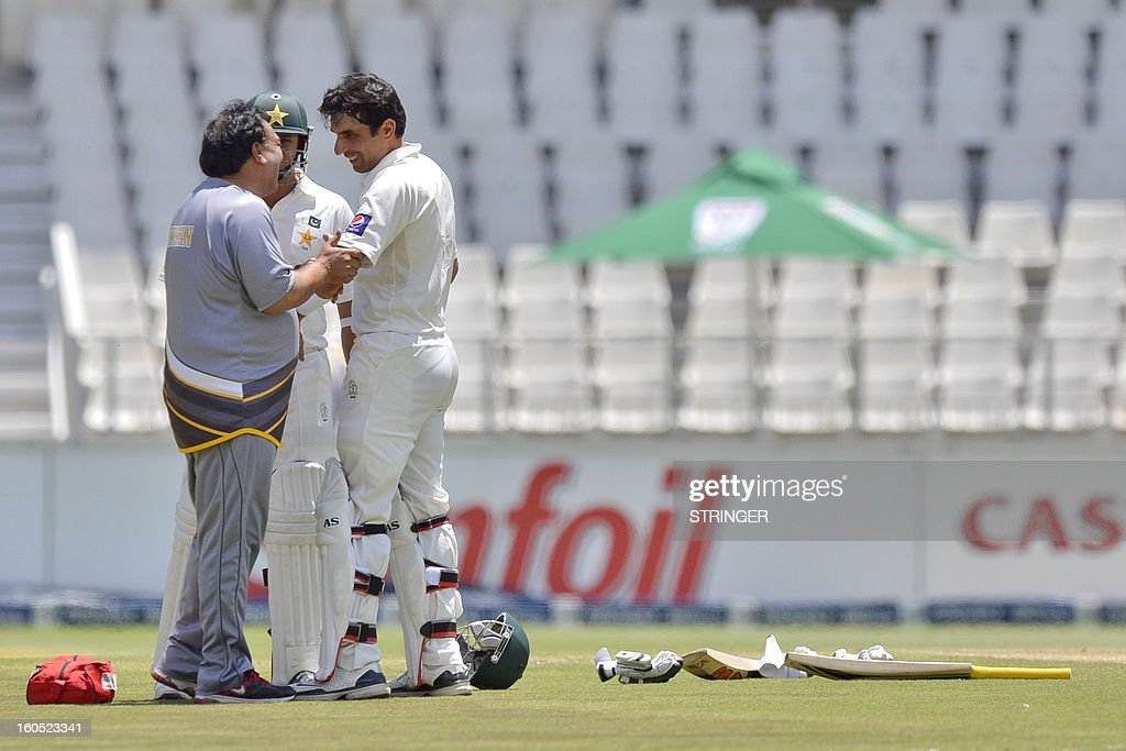 Misbah-ul-Haq from Pakistan (R) receives attention after the ball hit him on the elbow on day two of the first Test match between South Africa and Pakistan, in Johannesburg at Wanderers Stadium on Feb 2, 2013. AFP PHOTO / Stringer2