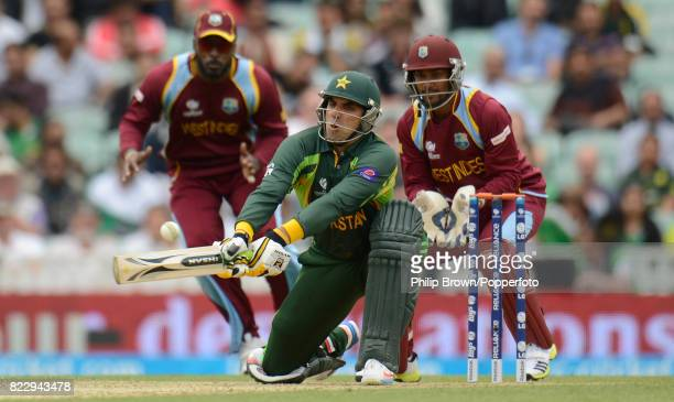 MisbahulHaq of Pakistan plays a reverse sweep during his innings of 96 not out watched by West Indies fielder Chris Gayle and wicketkeeper Denesh...