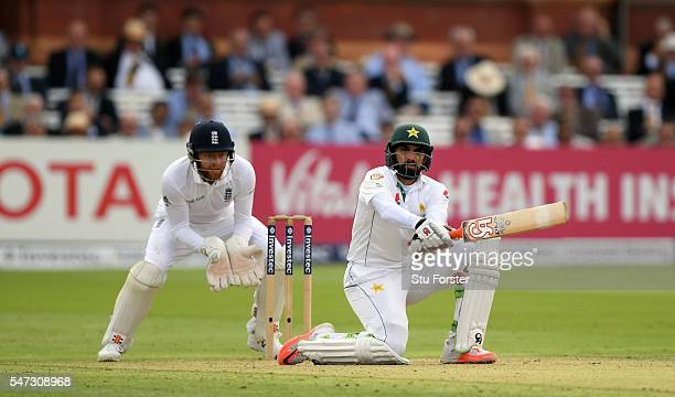 MisbahulHaq of Pakistan reverse sweeps a ball to the boundary watched by Jonny Bairstow during day one of the 1st Investec Test match between England...