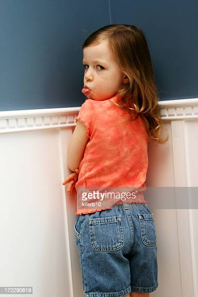 Misbehaved little girl, standing in corner, for a time out