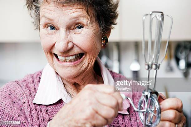 Mischievous old woman with egg beater smiles
