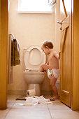 A mischievous toddler boy climbs into the toliet