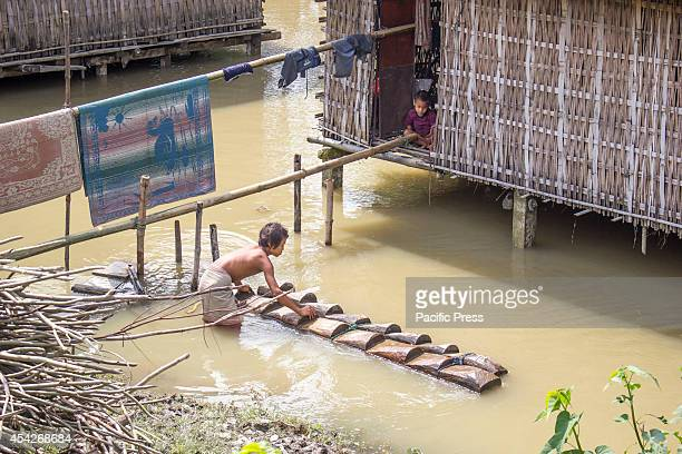 A mishing boy arranges a makeshift single bamboo bridge as his house is partially submerged by flood waters at Afala village at Disangmukh in...