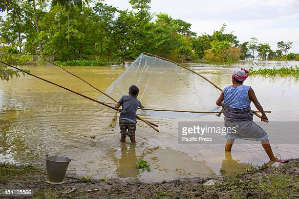 Mishing woman with her son fish using their handmade net on the floodwaters at Dikhowmukh in the Sivasagar district of Assam Monsoon rains caused...