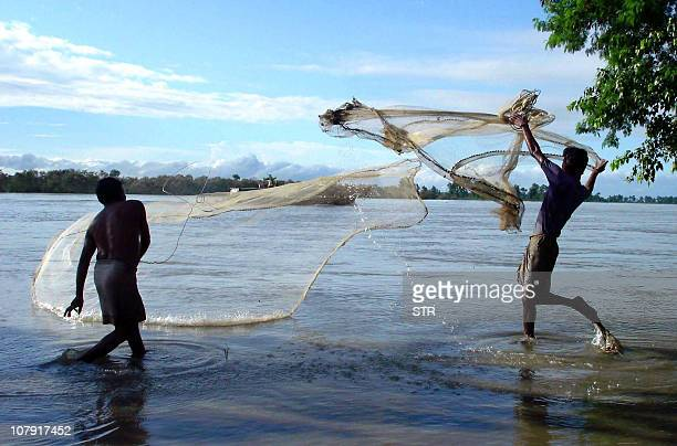 Mising tribal youths spread their fishing nets in the flood waters of the Disang river in the Sivasagar district of the northeastern state of Assam...