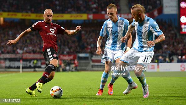 Miso Brecko of Nuernberg is challenged by Marius Wolf of Muenchen and Daniel Adlung of Muenchen during the second Bundesliga match between 1 FC...