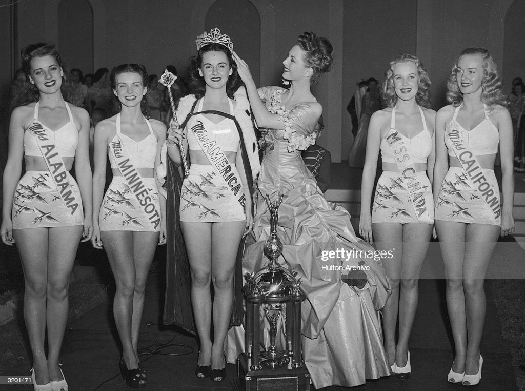 Miss America 1946 Marilyn Buferd crowns the new Miss America 1947 Barbara Jo Walker of Memphis Tennessee as five other contestants smile Atlantic...
