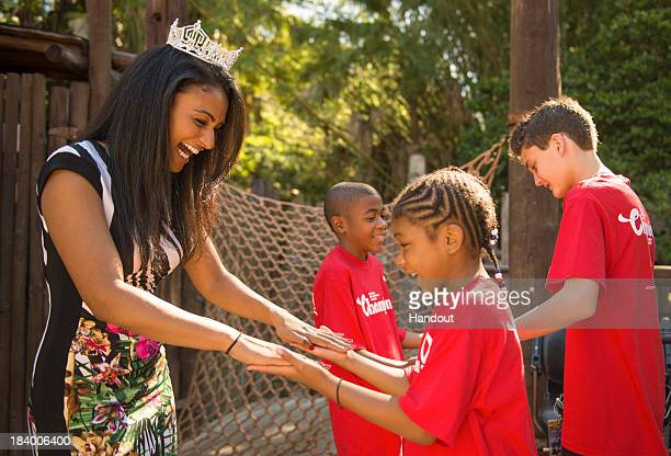 Miss America 2014 Nina Davuluri of Syracuse NY joins members of the 2013 'Champions of Children's Miracle Network Hospitals' at the Magic Kingdom at...