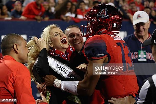 Miss Arizona USA Tommy Lynn Calhoun reacts after being knocked down by quarterback Brandon Dawkins of the Arizona Wildcats following a run play...