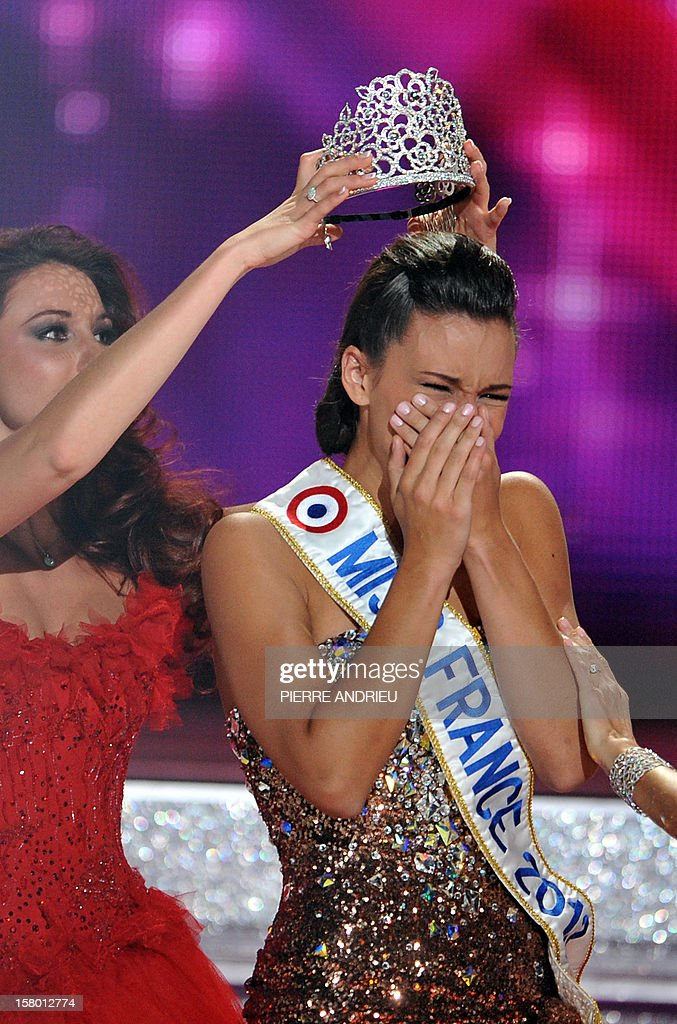 Miss Bourgogne Marine Lorphelin (R) crowned Miss France 2013 by Miss France 2012 Delphine Wespiser (L) during the 66th edition of the beauty contest in the central city of Limoges on December 8, 2012. AFP PHOTO / PIERRE ANDRIEU.