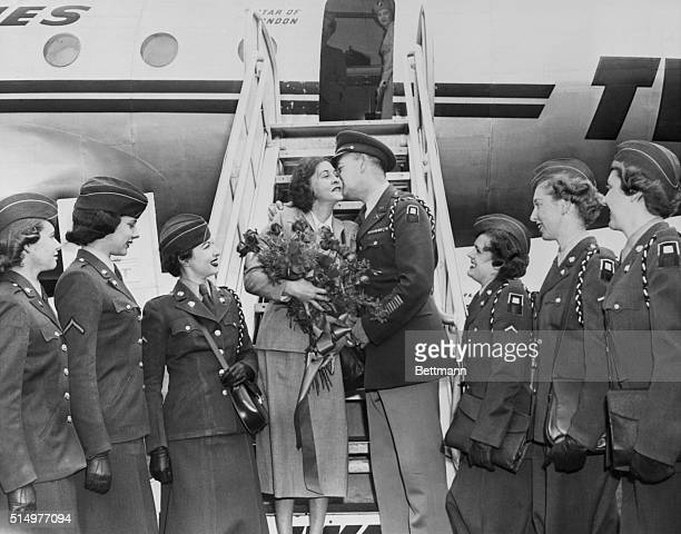 Miss Claire Phillips internationally known espionage agent is warmly greeted with a kiss and flowers by Major Kenneth Boggs and a WAC honor guard...