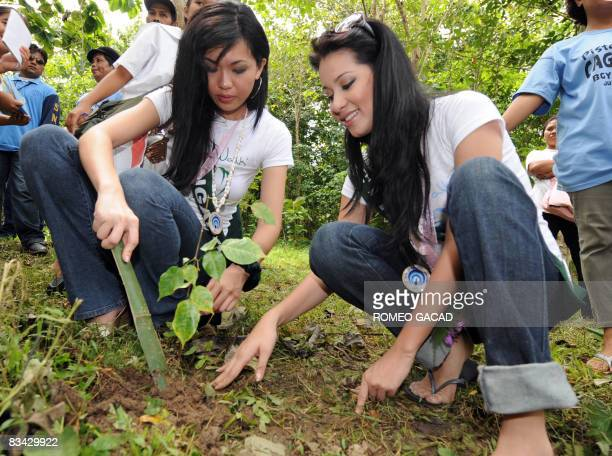 Miss Earth 2008 beauty contestants Ivy Leow Kian Peng from Singapore and Karla Henry of Philippines plant tree seedlings at the forest land of Puerto...