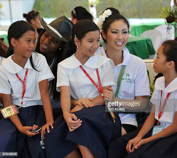 Miss Earth candidates Jennae Jackson of Jamaica and Tomomi Takada of Japan chat with elementary students after a tree planting activity at an upscale...
