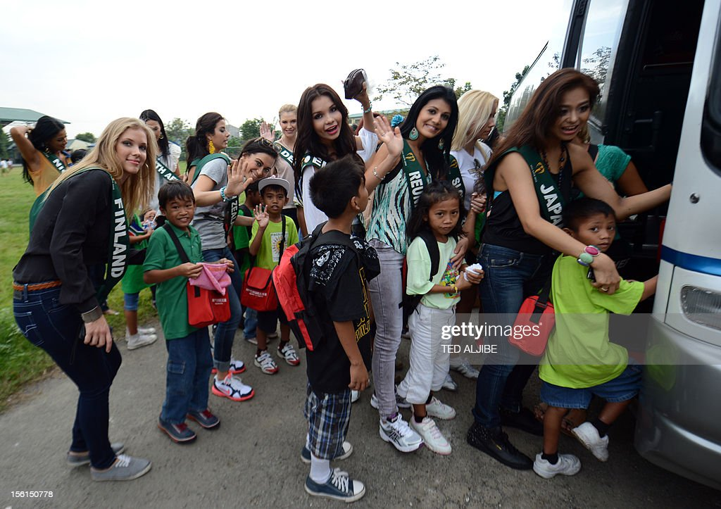 Miss Earth contestants walk with street children board a bus during a visit to a government-run shelter for street children in Manila on November 12, 2012. Around 91 contestants from around the globe will be vying for this year's crown, which will be held on November 24, in the country's capital city, with a theme in line with that of United Nations' (UN) celebration of the International Year of Sustainable Energy for all.