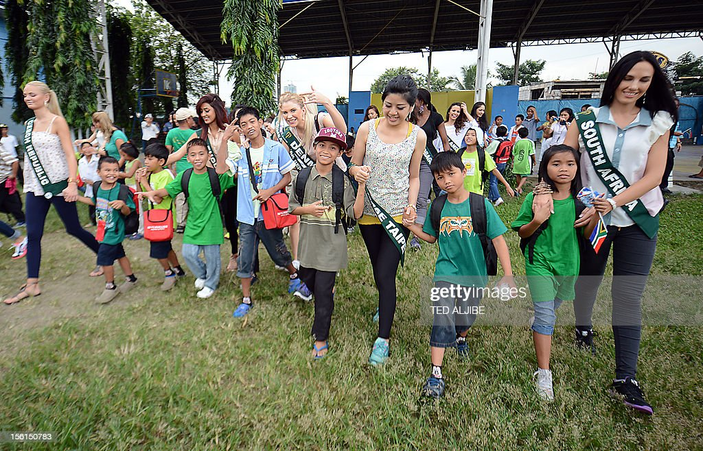 Miss Earth contestants walk with street children to a waiting bus during a visit to a government-run shelter for street children in Manila on November 12, 2012. Around 91 contestants from around the globe will be vying for this year's crown, which will be held on November 24, in the country's capital city, with a theme in line with that of United Nations' (UN) celebration of the International Year of Sustainable Energy for all.