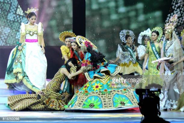 Miss Earth Philippines candidates help Miss Lucena City Shaine Louise Kim after fell down during the cultural costume parade in Miss Earth...